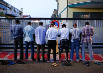 Migrants pray on a street after being removed from a building where they had been living in Rome