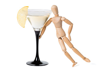 Wooden mannikin standing near glass of vermouth. Concept of drunkenness, alcohol abuse.