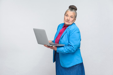 confused aged woman standing and holding laptop thinking and looking at camera. Grandmother in light blue suit with collected gray hair bun hairstyle. indoor, Studio shot, isolated on gray background