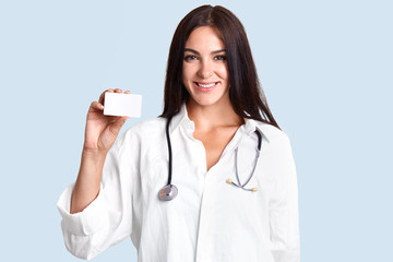 Beautiful professional female therapist wears white medical coat, stethoscope, holds blank card, smiles gently, isolated over light blue background. Medical worker models indoor. Medicine concept