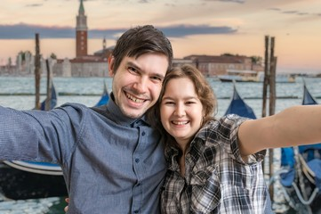 Young couple is taking selfie photo in Venice in Italy. Venetian gondolas in background.