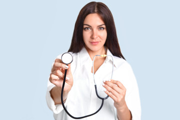 Isolated shot of prett confident female doctor advertises her new phonendoscope, ready to examine people, hear lungs and heart, isolated over blue background. Focus on stethoscope. Medical worker