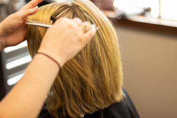 Blonde woman receiving haircut at a salon. Woman with blonde highlights. Hair foils on a female client. Master stylist cutting hair