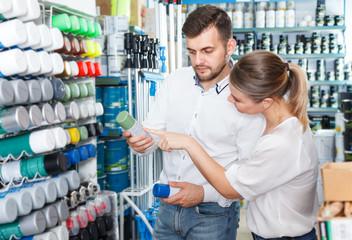 Couple choosing paint spray in shop