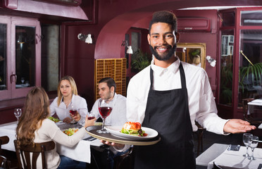 Smiling young cheerful waiter taking care of adults