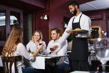 Smiling glad waiter taking care of adults