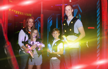 Parents and children playing laser tag in beams