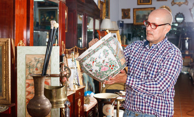 Portrait of mature man choosing vintage goods at antiques shop