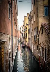 Gondola sails on the old narrow canal, Venice