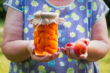 Senior woman holding glass jar of preserved apricots and ripe apricot in her hands