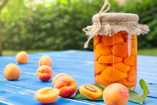 Homemade tasty apricot compote in glass jar and apricot fruit on blue wooden table
