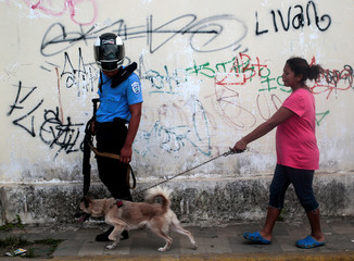 A local resident and her dog walk past a police officer in Diriamba