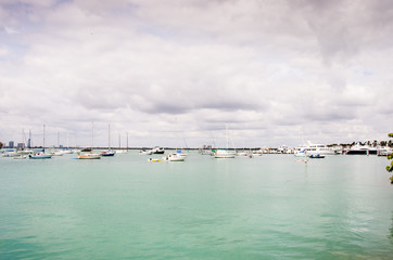 Boats on the blue water under a cludy sky