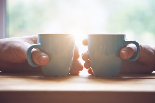 couple with two cups of morning coffee on sunrise light