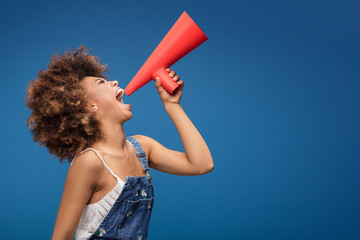 Teen girl screaming into red megaphone.