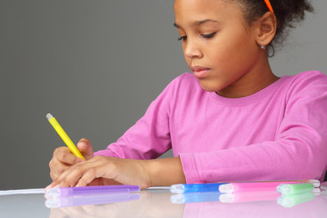 the girl draws a yellow pencil on white paper