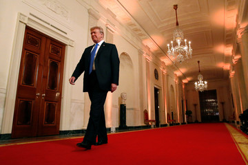 U.S. President Donald Trump walks in the East Room of the White House in Washington