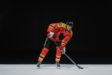 full length view of young professional sportsman playing ice hockey on black