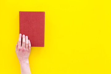 Reading concept. Reading as hobby. New knowledge. Hands take hardback book with empty cover on yellow background top view copy space