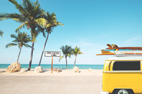 Vintage car with surfboard on roof on tropical beach in summer. beach sign for gone surfing. Vintage effect color filter.