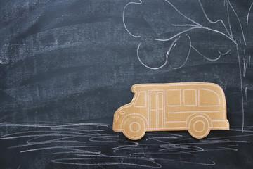 Back to school concept. Top view image cardboard school bus over classroom blackboard background.