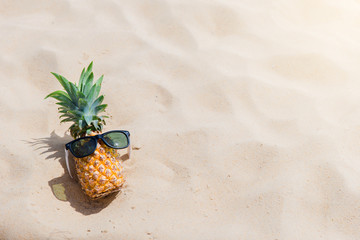 Fresh young pineapple lying on the sand beach background with sunglasses. Tropical vacation travel concept
