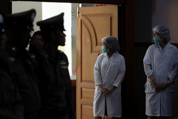 Police officers and nurses wearing protective attire attend a news conference at the Chiang Rai Prachanukroh hospital in Chiang Rai
