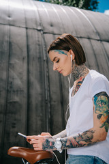 smiling tattooed woman in earphones listening music with smartphone while sitting on bicycle