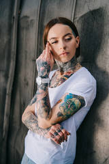 portrait of stylish young woman with tattoos looking away