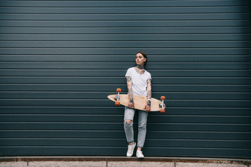 distant view of young woman with tattoos holding skateboard against black wall Wall mural