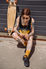 young tattooed woman in earphones listening music with smartphone near skateboard at street