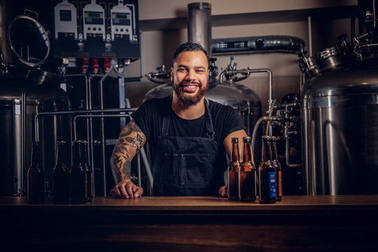 Portrait of a stylish bearded dark skinned male with a tattoo on his hand standing behind the counter in the brewery.