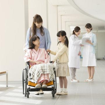 祖母の車椅子を押す親子