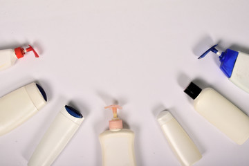 Plastic bottles of body care and beauty products on white background