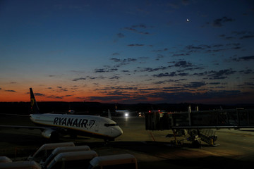 The moon is seen over a Ryanair airplane at the Adolfo Suarez Madrid Barajas airport in Madrid