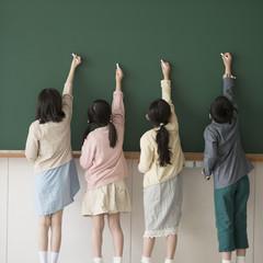 黒板に文字を書く小学生