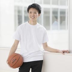 廊下でバスケットボールを持ち微笑む男子学生