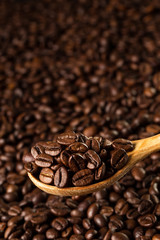 Roasted coffee beans in a wooden spoon.