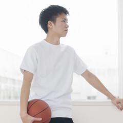 廊下でバスケットボールを持つ男子学生