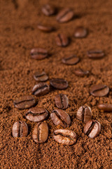 Coffee Beans macro on ground coffee background.