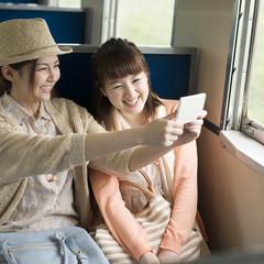 電車の中で写真を撮る2人の女性