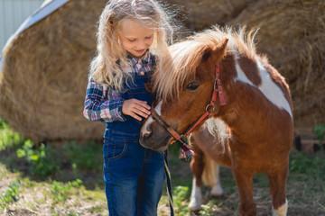 happy kid palming cute pony at farm