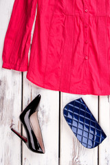 Horizontal cropped view pink shirt on white wooden background. Blue women's wallet and black shoe with heel.
