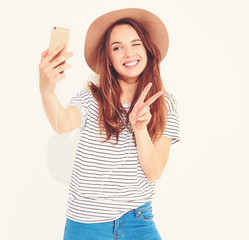 Portrait of a pretty girl in summer hipster clothes taking a selfie isolated on white background. Winking and showing peace sign