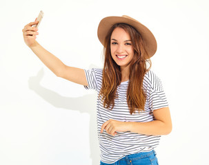 Portrait of a pretty girl in summer hipster clothes taking a selfie isolated on white background