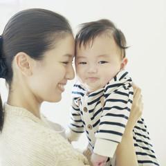 赤ちゃんを抱き微笑む母親