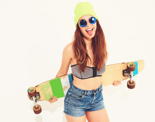 Portrait of young stylish smiling girl model in casual summer swimwear clothes and yellow beanie posing with longboard desk. Isolated on white, showing her tongue