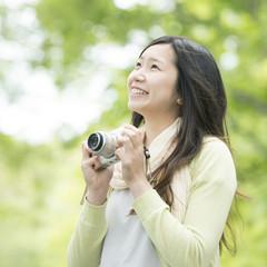 新緑の中でカメラを持ち微笑む女性