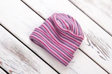 Striped winter hat. Flat lay, top view. White wooden desks surface background.