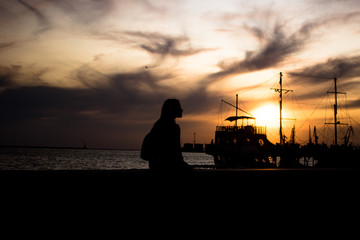 silhouette of a girl on the waterfront. silhouette of an old ship in the background. the girl is waiting for the ship